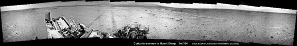 NASA's Curiosity rover make tracks to Mount Sharp (at left) across the floor of Gale Crater. The rover paused to image the windblown ripple at right, below the hazy crater rim. The wheel tracks are about eight  feet apart. This panoramic mosaic was assembled from a dozen navcam camera images taken on Sol 354 (Aug 4, 2013. Credit: NASA/JPL-Caltech/Ken Kremer Marco Di Lorenzo