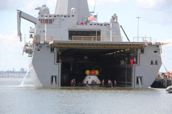 Dive teams haul Orion onto the well deck of the USS Arlington during Aug. 15 recovery test at Norfolk Naval Base, VA.  Credit: Ken Kremer/kenkremer.com