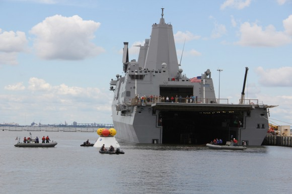 US Navy divers on four boats attached tow lines and to the Orion test capsule and guide it to the well deck on the USS Arlington during Aug. 15 recovery test Norfolk Naval Base, VA.  Credit: Ken Kremer/kenkremer.com