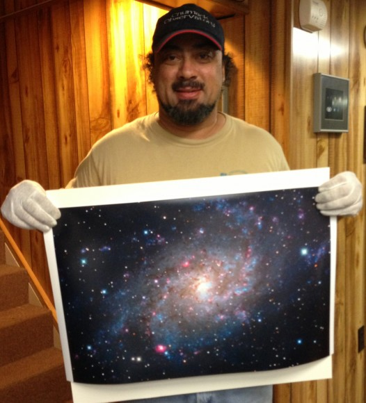 John Chumack's daughter Kayla took this picture of her Dad holding a 16x24 print of M33. Image courtesy of John Chumack.