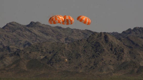 A test version of NASA's Orion manned  spacecraft descends under its three main parachutes above the U.S. Army Proving Ground in Arizona in the agency's most difficult test of the parachutes system's performance to prepare Orion for its first trip to space in December 2014.  Credit:  NASA/Rad Sinyak
