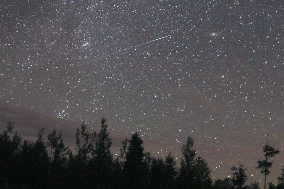 A fine Perseid flashes straight out of the radiant on August 12, 2013. The fuzzy-starry clump near the start of the trail is the Double Cluster. Credit: Bob King